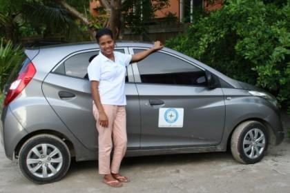Burlee Zaldivar, Founder of ecploring roatan standing next to a car with the exploring roatan logo