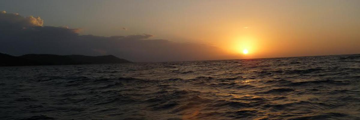 sun setting over the ewater in Roatan Honduras