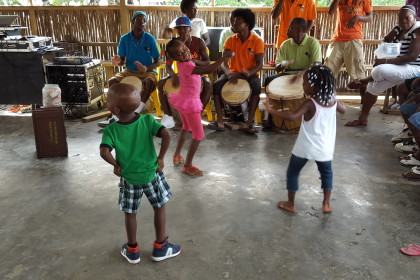 children dance while a traditional Garifuna drum line perform